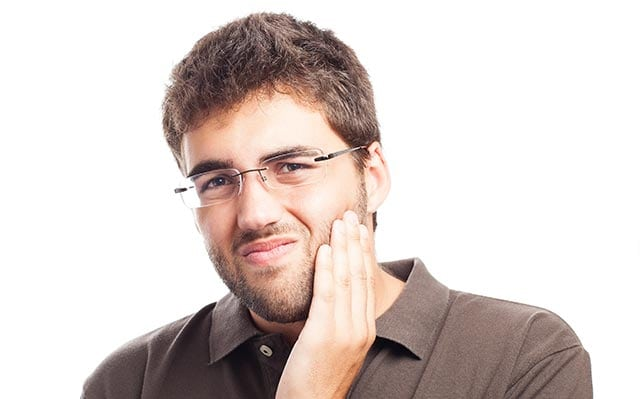 man holding his jaw considering alternatives to soda