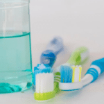white counter with glass of turquoise mouthwash and three toothbrushes